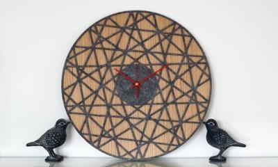 ažūrinis sieninis laikrodis interjere